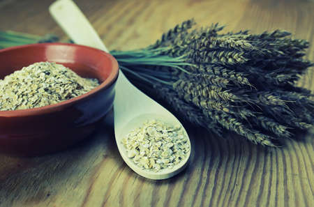 sorgo: milled wheat in clay pots on a wooden table and a bouquet of dry wheat Foto de archivo