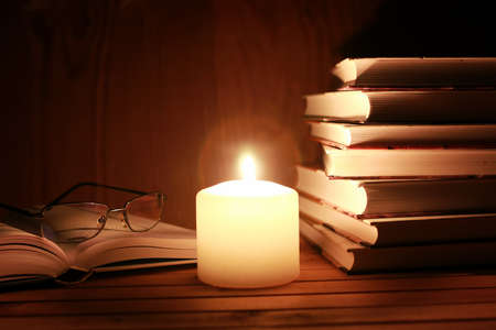 book and glasses on a table with candle light in night