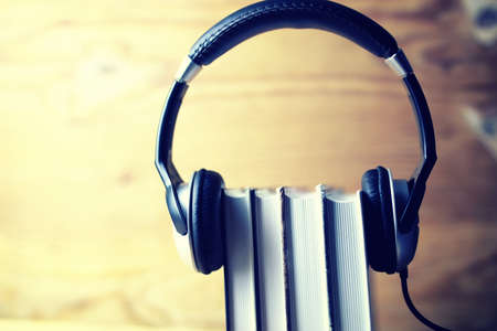 audio book: the concept of using audio books put on the headphones on the book on the background of wooden wall