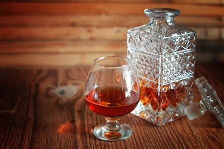 brandy: glass with sustained strong alcohol brandy on a wooden table Stock Photo
