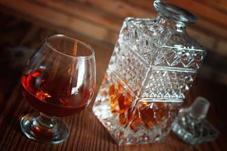 glass with sustained strong alcohol brandy on a wooden table Stock Photo