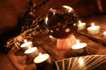 crystal ball for predicting the fate and supernatural action on the table from the old mahogany with candles and cards 免版税图像