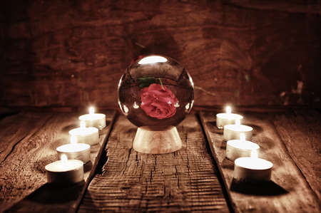 esoterism: crystal ball for predicting the fate and supernatural action on the table from the old mahogany with candles and cards Stock Photo
