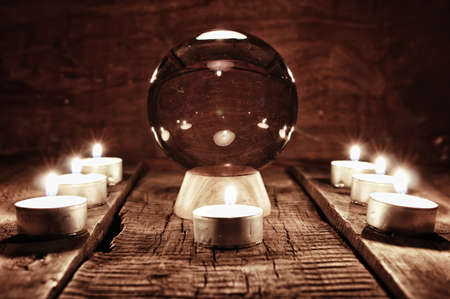 palmistry: crystal ball for predicting the fate and supernatural action on the table from the old mahogany with candles and cards Stock Photo