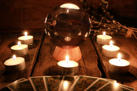crystal ball for predicting the fate and supernatural action on the table from the old mahogany with candles and cards Standard-Bild
