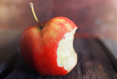 bitten: red bitten apple on an old  wooden background
