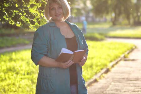 overweight students: portrait of a nice girl on a sunny summer day in the city streets
