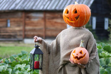 surrealistic: girl with a carved pumpkin on her head   for Halloween Stock Photo