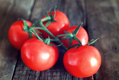 red tomatoes   on  wooden background