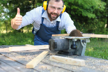 bearded handsome man in working clothes cut on the circular saw Stock Photo