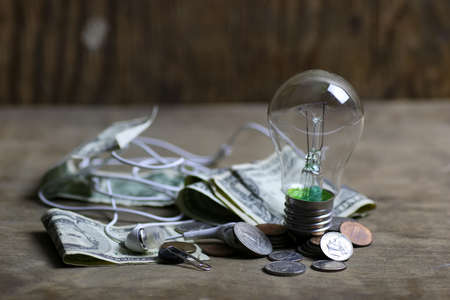 excessive: concept of excessive cost of electricity incandescent lamp and money on the table