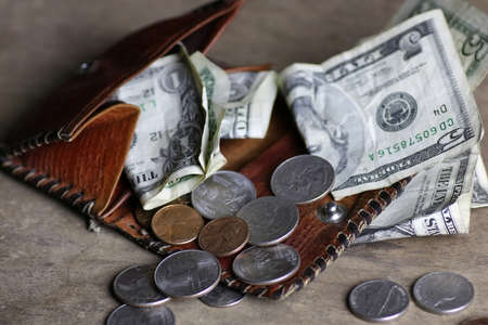 change purse: money on a wooden table bills and coins pocket change