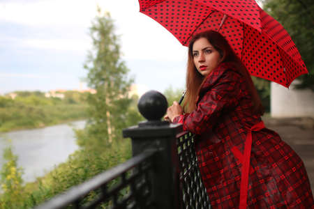 beautiful girl in a red raincoat with an umbrella walks in the rain Stock Photo