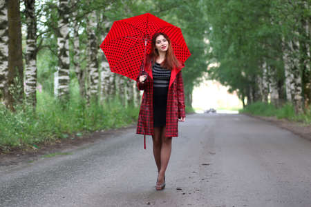 beautiful girl in a red raincoat with an umbrella walks in the rain Stock Photo