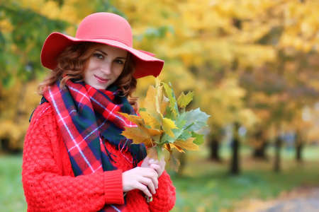 woman wearing red hat in autumn park