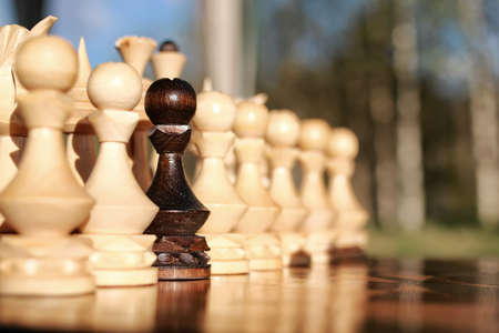 pawns: sun glare on the figures in the figures chess board in the park spring evening Stock Photo