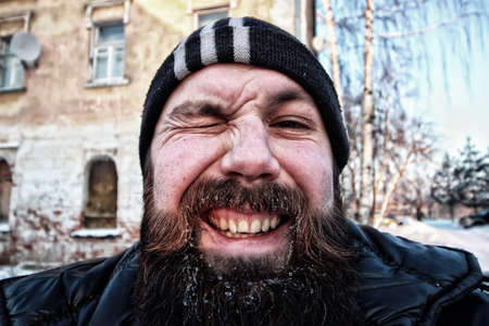 unhappy man: bearded dirty man in a sunny winter macro portrait