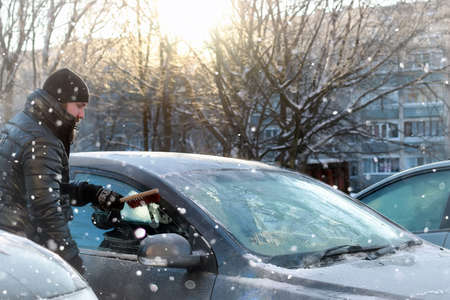 a bearded man in a black down jacket cleans a car from the snow