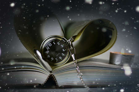 book made up in shape of heart and pocket retro watches candles Stock Photo