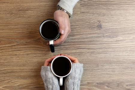 Dos amantes que llevan a cabo las manos de cada uno y de tomar café en la mesa Foto de archivo - 65073733