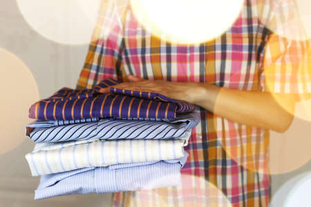 pile of mans ironing shirts in a stack and hand