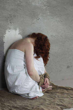 adult rape: Portrait of a young red-haired girl on a background of gray plaster wall