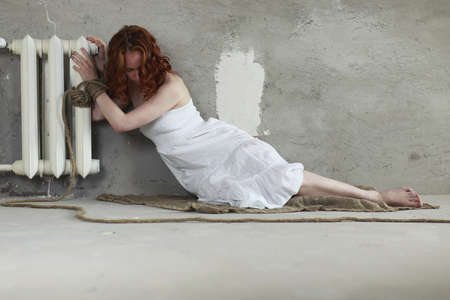 bounded: Portrait of a young red-haired girl on a background of gray plaster wall