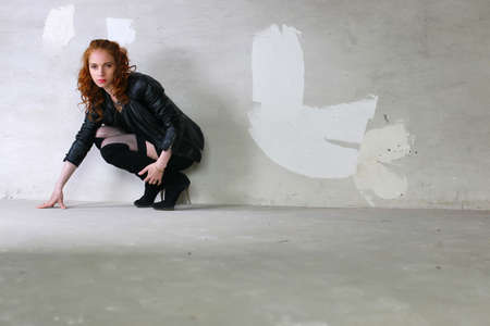 torn stockings: Portrait of a young red-haired girl on a background of gray plaster wall