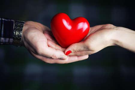ragazza innamorata: oggetto a forma di cuore mani rosse in possesso di un giovane Archivio Fotografico