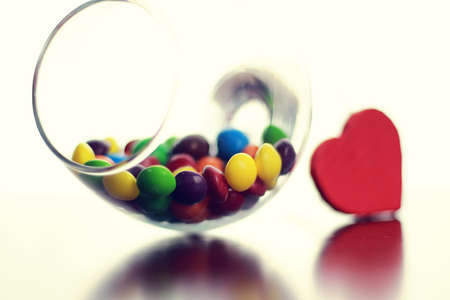 colored jelly beans and candy in a glass transparent glass on a table