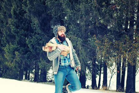 winter wood: bearded handsome man went into the forest with an ax to produce wood for the furnace