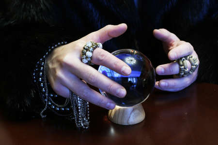 esoterism: sorcerer hands over a transparent crystal ball fortune-telling for the future