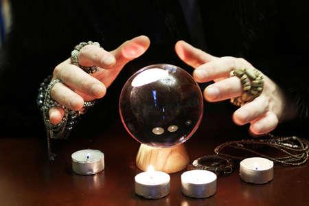 마법사는 미래를위한 투명한 수정 구슬 점쟁이를 넘겨 준다.