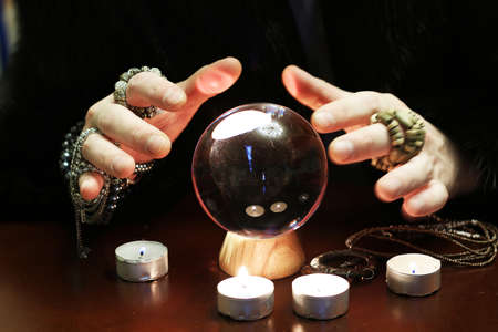 astrologist: sorcerer hands over a transparent crystal ball fortune-telling for the future