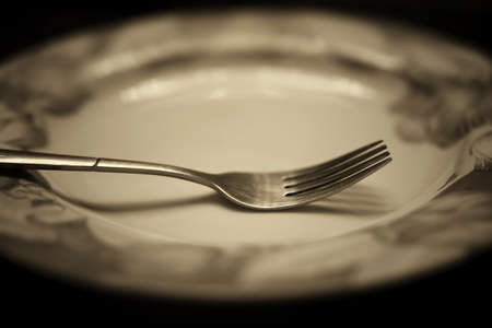 grunge flatware: black and white picture fork on an empty plate dining