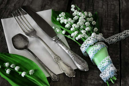 antiques: old shabby wooden painted background and a beautiful bouquet of fresh white flowers lily of the valley