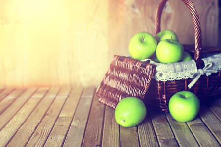 fruits in a basket: fresh green juicy apples in a basket on a wooden table rustic Stock Photo