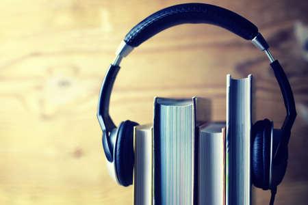 나무 벽의 배경에 책에 헤드폰에 넣어 오디오 책을 사용하는 개념