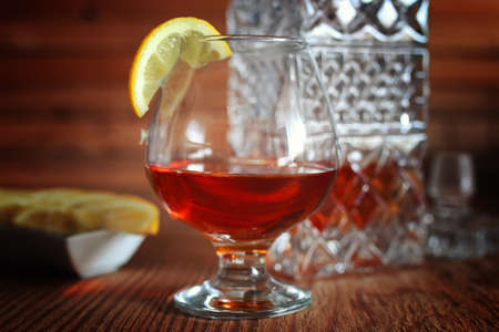 snifter: glass with sustained strong alcohol brandy on a wooden table Stock Photo