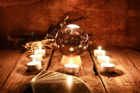 Kristallkugel das Schicksal und übernatürliche Wirkung auf den Tisch aus dem alten Mahagoni mit Kerzen und Karten für die Vorhersage Standard-Bild
