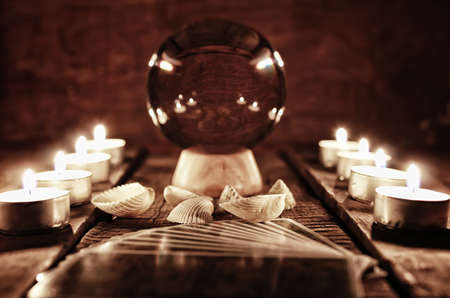 astrologist: crystal ball for predicting the fate and supernatural action on the table from the old mahogany with candles and cards Stock Photo
