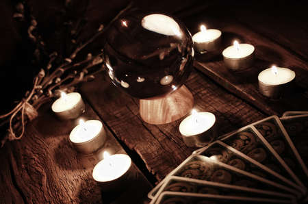 palmist: crystal ball for predicting the fate and supernatural action on the table from the old mahogany with candles and cards Stock Photo