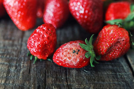 noxious: juicy flavorful red ripe strawberry on a wooden natural background Stock Photo