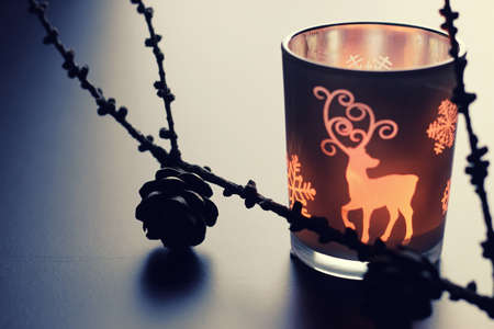 cor: home d cor on the table candle in a glass lamp and dry larch branch Stock Photo