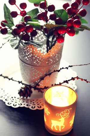 d cor: home d cor on the table candle in a glass lamp and dry larch branch Stock Photo