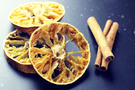 slices of dried orange and cinnamon sticks aromatic on black table
