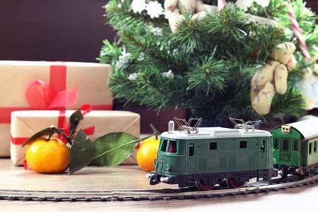 kleine oude speelgoed trein op de baan en met een motor onder de kerstboom versierd Stockfoto