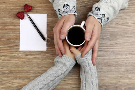 two lovers holding each other's hands and drinking coffee at the table
