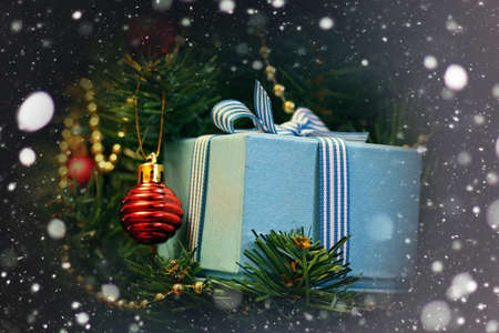 Christmas gift in the blue box with a bow with a bright-colored toys
