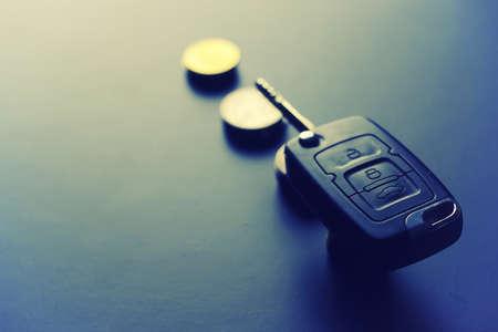 Black keychain car key on a matt black background and money